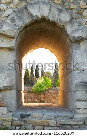 Exit in the ancient wall. Entrance to the green park - stock photo