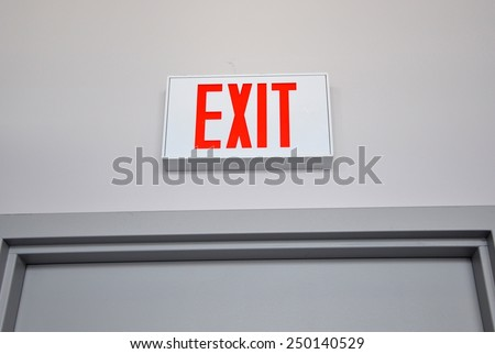 Exit sign above the door - stock photo