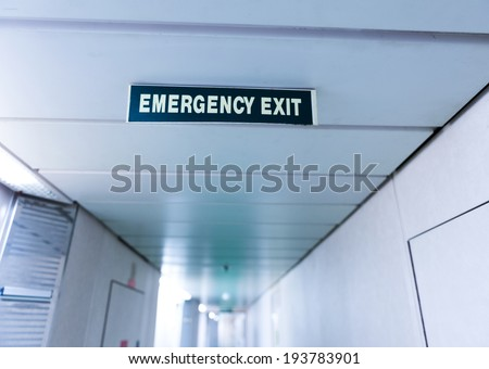exit sign suspended from the ceiling of cruise ship corridor. - stock photo
