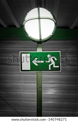 Exit sign with industrial lamp - stock photo