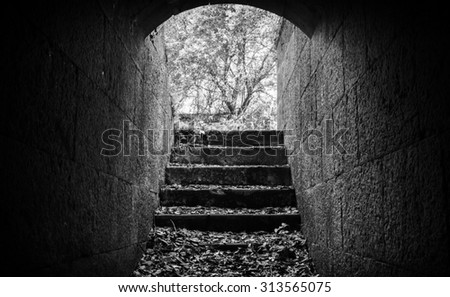 Exit with stairs from dark abandoned concrete tunnel interior - stock photo
