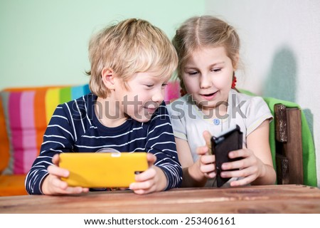 Exited pretty girl showing boy into screen of cellphone - stock photo