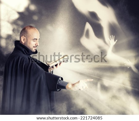 Exorcist priest fights a demon in a dark room - stock photo