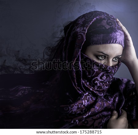 Exotic arab woman looking outside. artistic portrait with handmade tattoo tribals, blue tone in the background - stock photo
