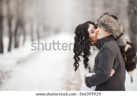 Exotic asian bride and groom kissing in middle of snowy winter alley. Young man in winter coat and fur hat, bride in white wedding dress with sheepskin. Cold season warm clothing. Copy space for text. - stock photo