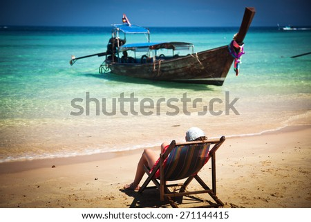 Exotic beach holiday background with woman sitting in  beach chair and long tail boat - Thailand ocean landscape - stock photo