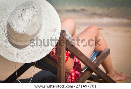 Exotic beach holiday - woman in beach chair and hat - stock photo