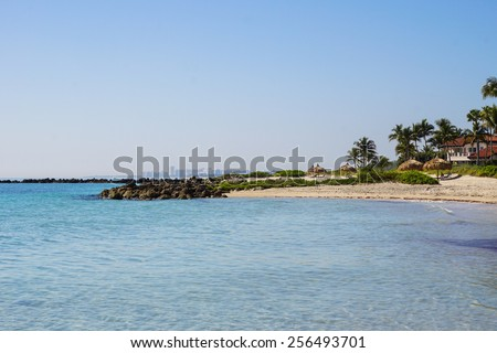 Exotic Beach, Resort with Straw Umbrellas/ Loungers - stock photo