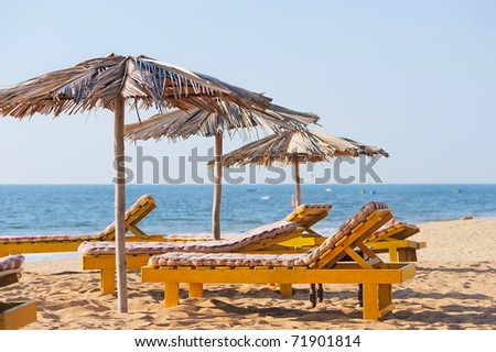 Exotic beach umbrellas and chairs on tropical coast - stock photo