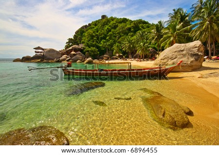 Exotic beach with long-tailed boat anchored at the shore - stock photo