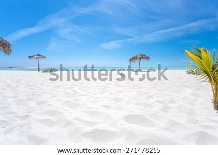 Exotic beach with white sand and umbrellas made of palm leafs  in Cayo Largo island - stock photo