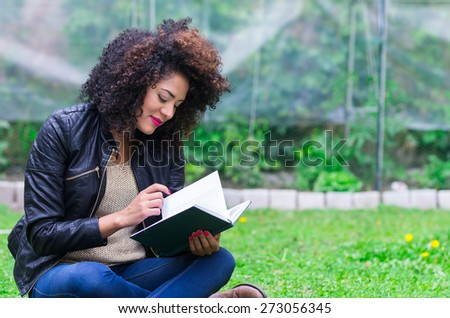 exotic beautiful young girl with dark curly hair relaxing in the garden reading a book - stock photo