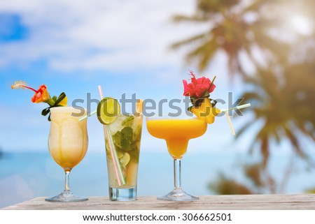 Exotic cocktails in outdoor cafe tropical setting at sunset - stock photo