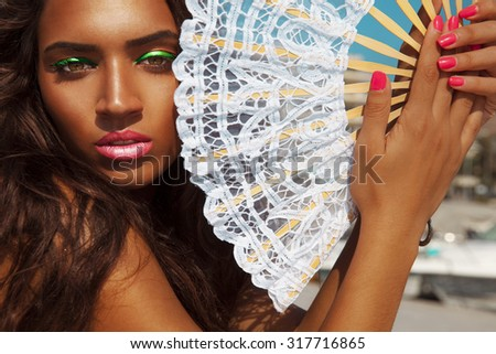 Exotic female posing on a hot summer day with fan and colorful pink makeup. Beauty and fashion . Toned in warm colors. Horizontal, summer shot. outdoors. - stock photo