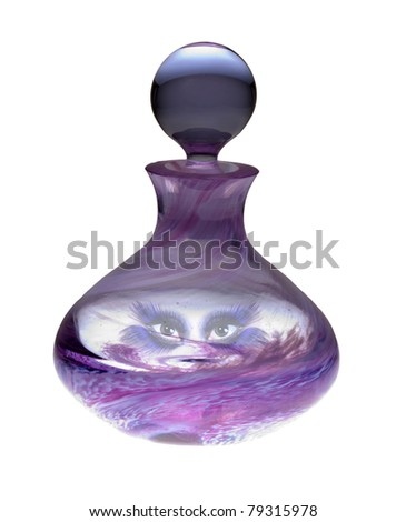 Exotic genie eyes peering out from the inside of a colored glass perfume bottle. - stock photo