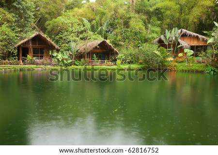 exotic huts in front of a lake in the rainy season - stock photo