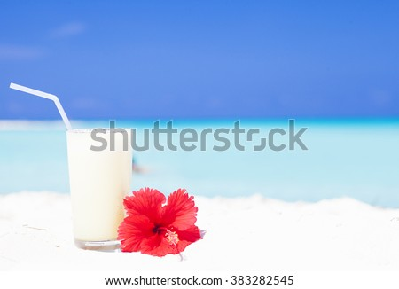 exotic pina colada cocktail near white sand beach