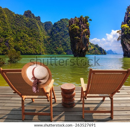 Exotic rest in Thailand. The coast of the gulf in the Andaman Sea. Two chaise lounges and an elegant hat on one - stock photo