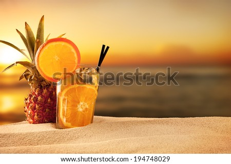 Exotic summer drink with sea shells, blur sandy beach on background - stock photo