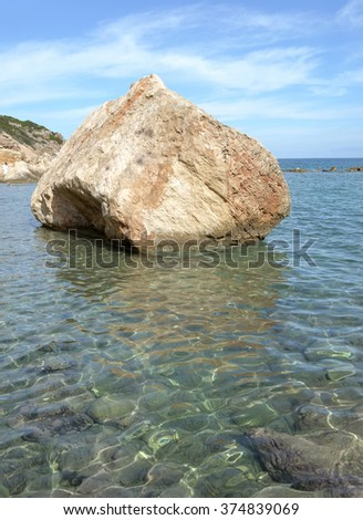 Exotic Travel Beach Scene - Boulder in the ocean - stock photo