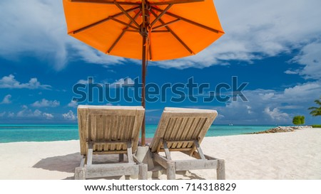 Exotic tropical beach landscape with two beach chairs and umbrella under the blue sky for background or wallpaper. Design of tourism for summer vacations concept. Luxury travel destination
