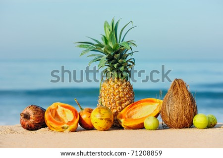 Exotic tropical fruit on the sandy shore - stock photo
