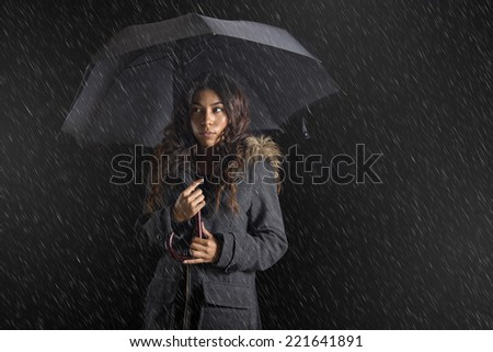 Exotic woman holding an umbrella in the rain - stock photo