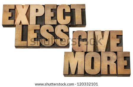 expect less, give more - motivation or self improvement concept - isolated words in vintage letterpress wood type blocks