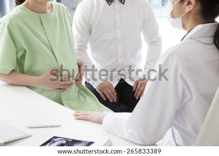 Expectant couple talking while counseling doctor in clinic - stock photo