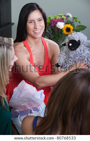 Expectant mom with friends holds baby shower gift - stock photo