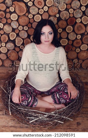Expectant mother in the studio. Pregnant girl on a wooden background cut, are sitting in the nest. - stock photo