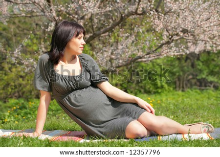 expectant mother is dreaming about future in blossom garden - stock photo