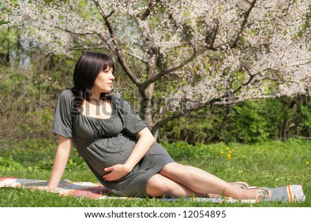 expectant mother is having a rest under blossom apple tree, solar springtime - stock photo