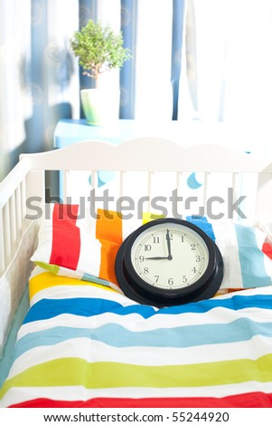 expecting baby - little bed with clock at nine month time - stock photo