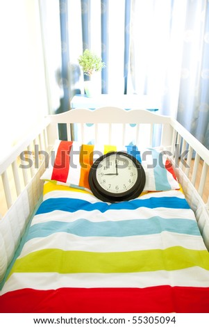 Expecting child - baby bed and clock as symbol of expectation - stock photo