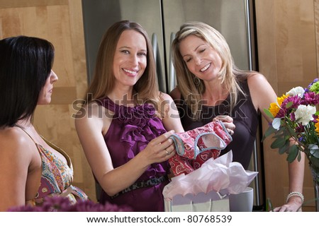 Expecting mom with friends holds baby clothes