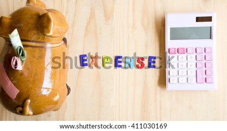 Expense word with piggy bank and calculator on wooden background - stock photo