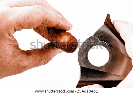 Expensive cigar and cutter in man hand on a white background - luxury lifestyle - stock photo