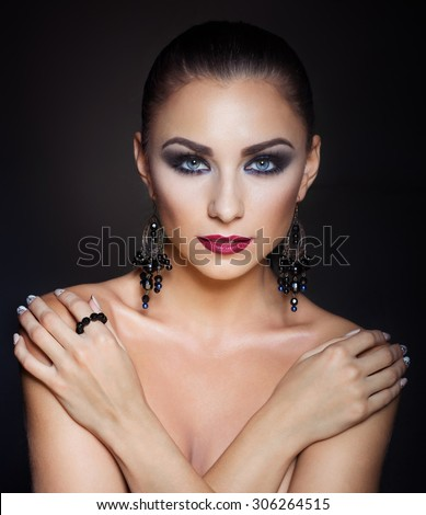 expensive jewelry wreath earrings and ring on a beautiful sexy nude elegant brunette girl with bared shoulders with bright evening make-up