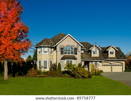 Expensive luxury home against a blue sky in a autumn season - stock photo