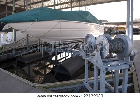 Expensive pleasure boat safely stored under canopy on a hyrdolic lift in a dock - stock photo
