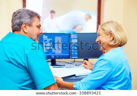 experienced adult medical stuff talking about patient diagnosis in tomography room - stock photo