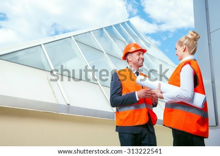 Experienced architects are standing and discussing new project. They are smiling. The woman is holding a blueprint. Copy space in left side - stock photo
