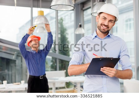 Experienced builders are doing their work. The young architect is standing and holding a folder of documents. He is writing and smiling. The senior worker is adjusting the lamp with screwdriver - stock photo