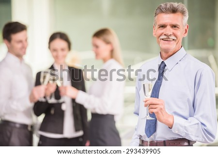 Experienced business man celebrating his success, team on background. - stock photo