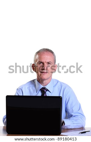 Experienced businessman looking up from his work - stock photo