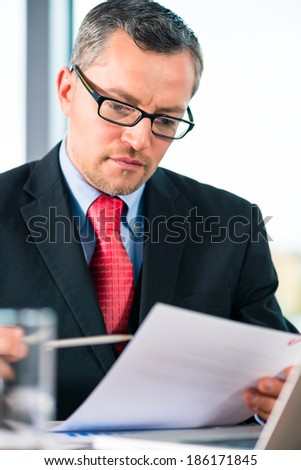 Experienced businessman or lawyer sitting in the Office at desk and working with document or contract - stock photo