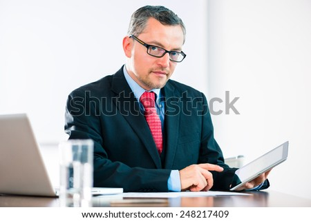Experienced businessman or lawyer sitting in the Office at desk and working with document or contract on laptop or computer - stock photo