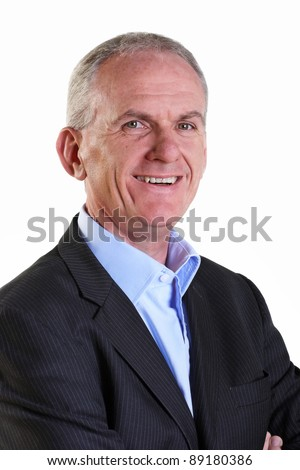 Experienced businessman smiling with arms folded - stock photo