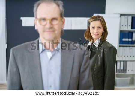 experienced businesswoman with her co-worker standing in the office - stock photo